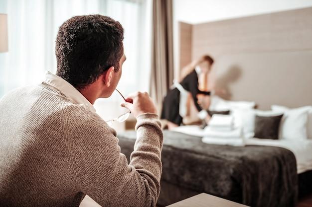 Piani per molestie. uomo d'affari con pensieri sporchi che hanno piani per molestie guardando cameriera sexy