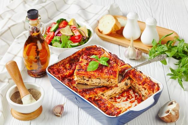 Lasagne a base di piante con tofu, funghi, salsa di passata in una teglia servite con una fresca insalata di lattuga, pomodoro, cetriolo, cipolla rossa e foglie di basilico su una superficie di legno bianco, primo piano