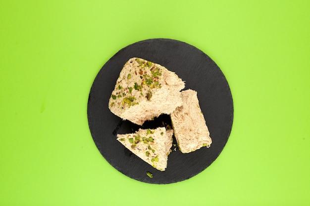 Pistacchi a base vegetale halva su pietra nera dolci orientali sfondo verde spazio copia