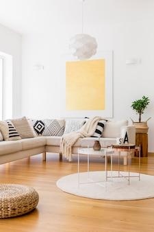 Pianta in cesto intrecciato su sgabello in legno in soggiorno con pittura in oro su parete bianca