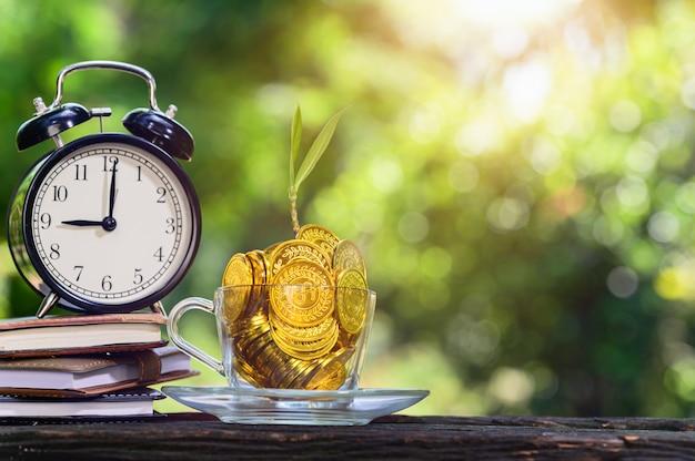 Pianta che cresce in monete di risparmio sfondo verde bokeh con luce solare