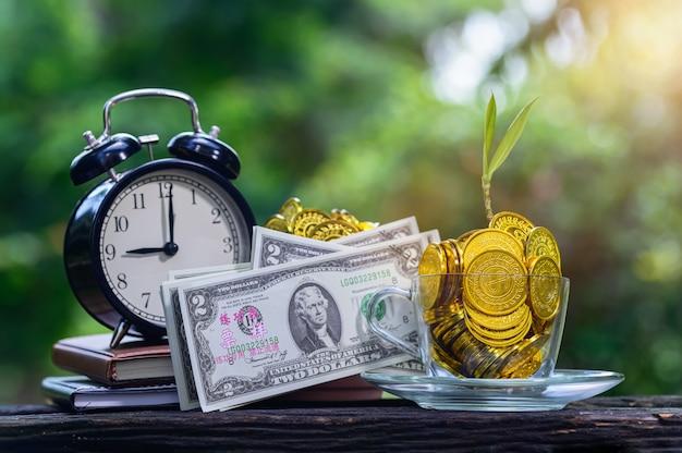Pianta che cresce in monete di risparmio bokeh verde con luce solare