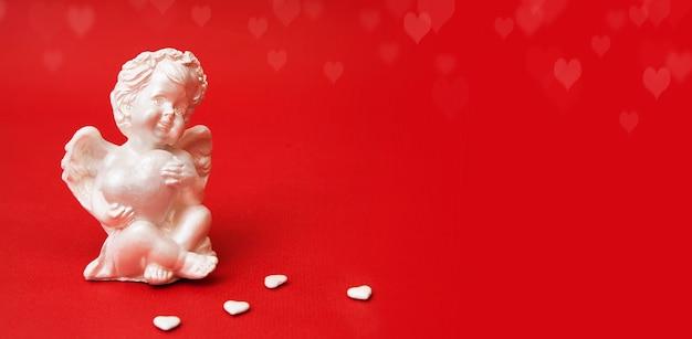 Statuetta in gesso di un angelo con un cuore su una superficie rossa