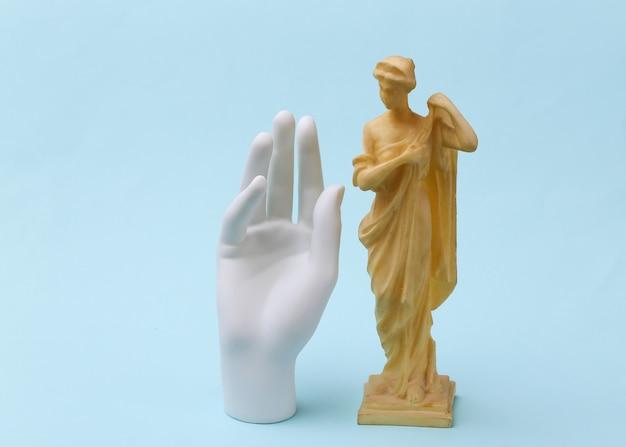 Mano in gesso e statua antica su sfondo blu.