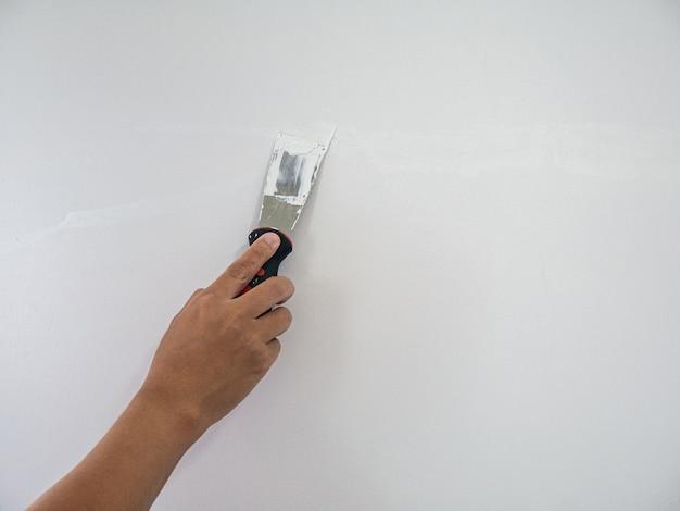 Mano di stuccatore riparazione crepa muro bianco