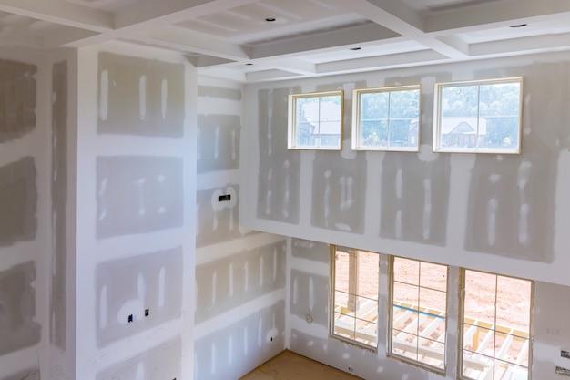 Intonacatura del muro a secco nuova industria domestica sulla finitura dello stucco nei pannelli in cartongesso delle pareti della stanza