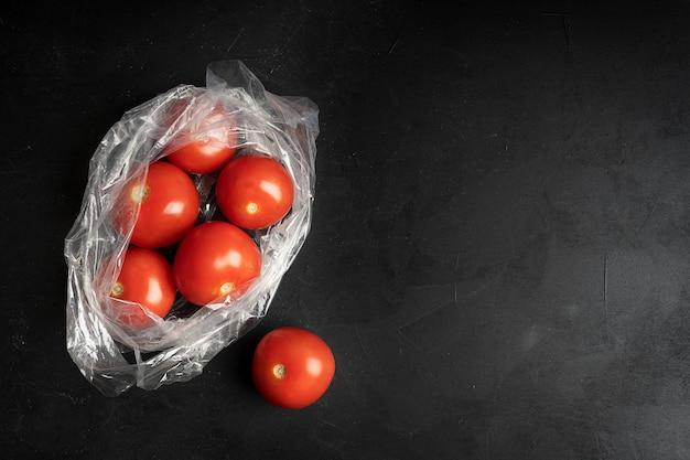 Sacchetto di plastica pieno di pomodori maturi sul nero scuro