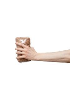 Sacchetto di plastica tenuto in mano isolato su bianco. uomo che tiene confezione di grano saraceno
