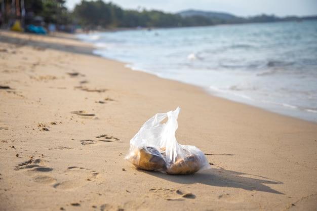 Sacchetto di plastica che si trova su un inquinamento ambientale della spiaggia tropicale sabbiosa