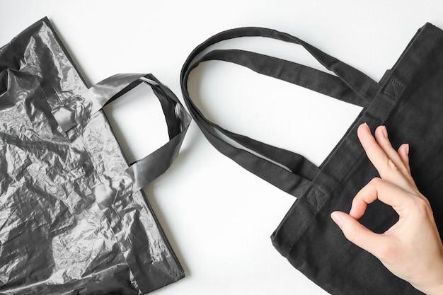 Sacchetto di plastica e sacchetto di tessuto su un tavolo bianco oggetti riutilizzabili senza plastica