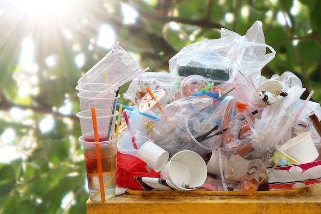 Spreco di sacchetti di plastica un sacco di spazzatura su sfocatura dello sfondo sole albero
