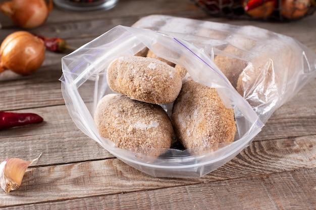 Sacchetti di plastica con carne congelata e cotolette in un sacchetto di plastica su un tavolo di legno