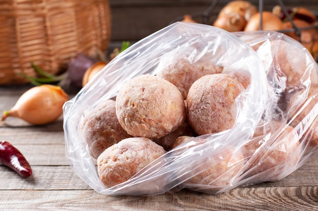 Sacchetti di plastica con carne congelata e polpette di carne in un sacchetto di plastica su un tavolo di legno