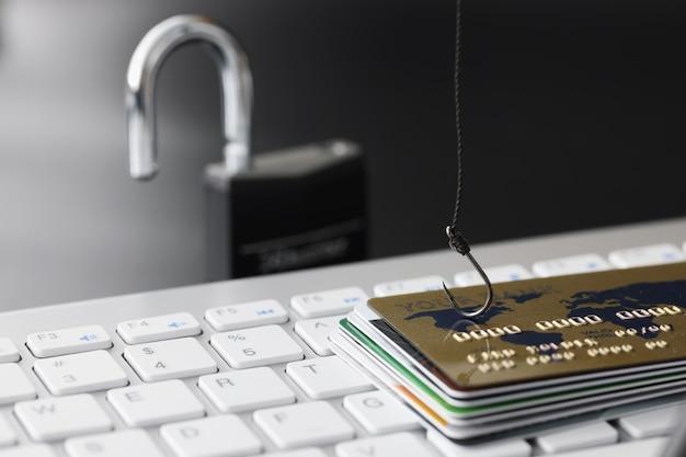 Carte di credito bancarie di plastica e amo da pesca sul concetto di dipendenza da shopping online della tastiera del computer