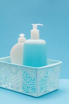 Cestino di plastica con bottiglie di detersivo per piatti, detergente per vetri e piastrelle su sfondo blu. prodotti per il lavaggio e la pulizia.