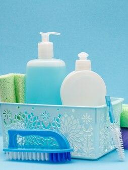 Cestino di plastica con bottiglie di detersivo per piatti, detergente per vetri e piastrelle, spazzole su sfondo blu. prodotti per il lavaggio e la pulizia.
