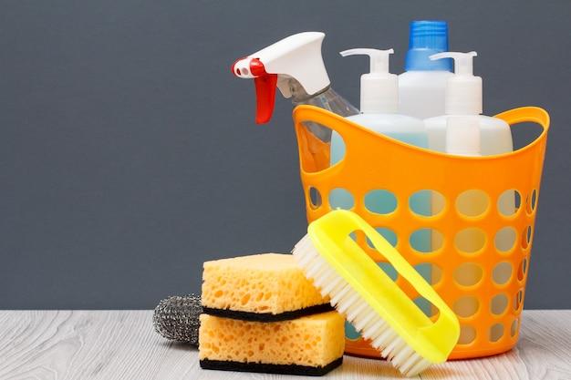 Cestello in plastica con flaconi di detersivo per piatti, detergente per vetri e piastrelle, detersivo per forni a microonde e fornelli. spazzola e spugne su sfondo grigio. concetto di lavaggio e pulizia.