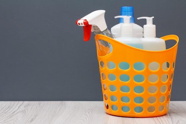 Cestino di plastica con bottiglie di detersivo per piatti, detergente per vetri e piastrelle, detergente per forni a microonde e stufe su sfondo grigio con spazio di copia. concetto di lavaggio e pulizia.