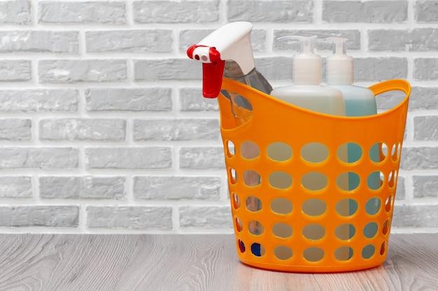 Cestino in plastica con flaconi di detersivo per piatti, detergente per vetri e piastrelle, detersivo per forni a microonde e fornelli con un muro di mattoni sullo sfondo. concetto di lavaggio e pulizia.