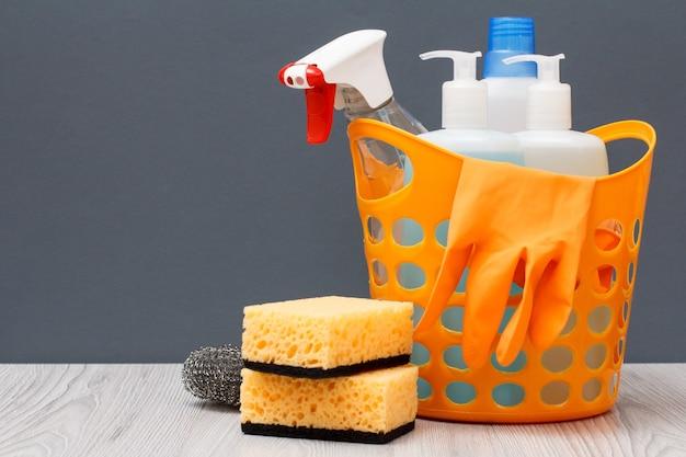 Cestino in plastica con guanto protettivo, flaconi di detersivo per piatti, detergente per vetri e piastrelle, detersivo per forni a microonde e fornelli, spugne su sfondo grigio. concetto di lavaggio e pulizia.