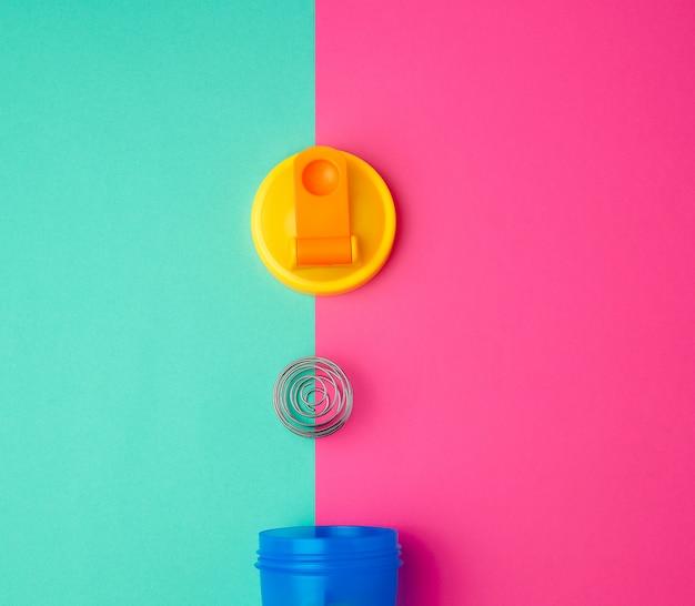 Bottiglia di plastica blu shaker con un tappo giallo e una palla di ferro per gli sportivi