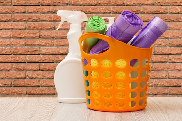 Bottiglia di plastica di detersivo per piatti, un cesto con sacchetti della spazzatura, spugne e un muro sullo sfondo. concetto di lavaggio e pulizia.