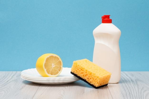 Bottiglia di plastica di detersivo per piatti, piatti puliti, limone e spugna su sfondo blu. concetto di lavaggio e pulizia.