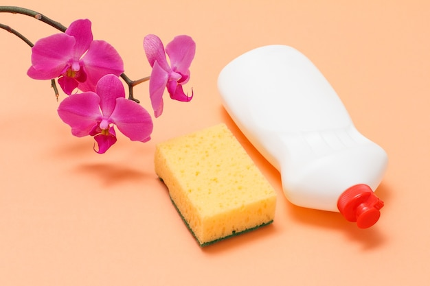 Bottiglia di plastica di detersivo per piatti, una spugna e fiori di orchidea su fondo beige. vista dall'alto. set di lavaggio e pulizia.