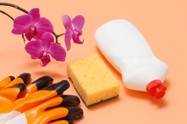 Bottiglia di plastica di detersivo per piatti, spugna, guanti di gomma e fiori di orchidea su fondo beige. vista dall'alto. set di lavaggio e pulizia.