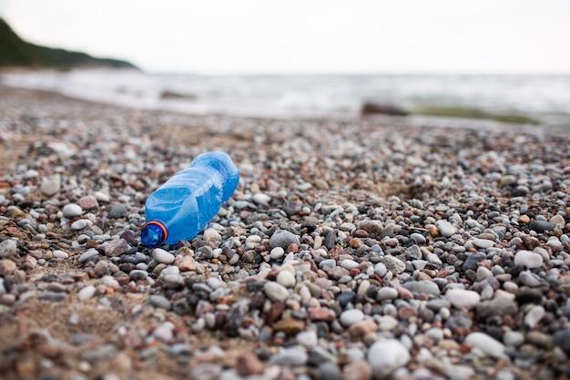 Una bottiglia di plastica è in ferie in spiaggia dal turista. ecologia, immondizia, inquinamento ambientale
