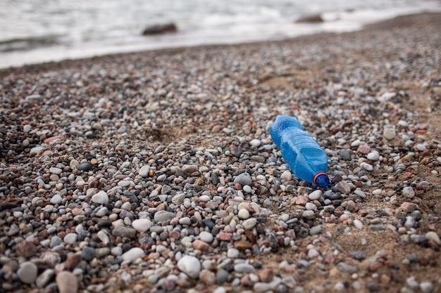 Una bottiglia di plastica è in ferie in spiaggia dal turista