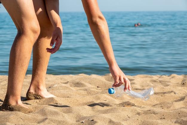 La bottiglia di plastica è sulla spiaggia lasciata dal turista