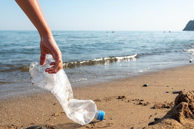 La bottiglia di plastica è sulla spiaggia lasciata dal turista Foto Premium