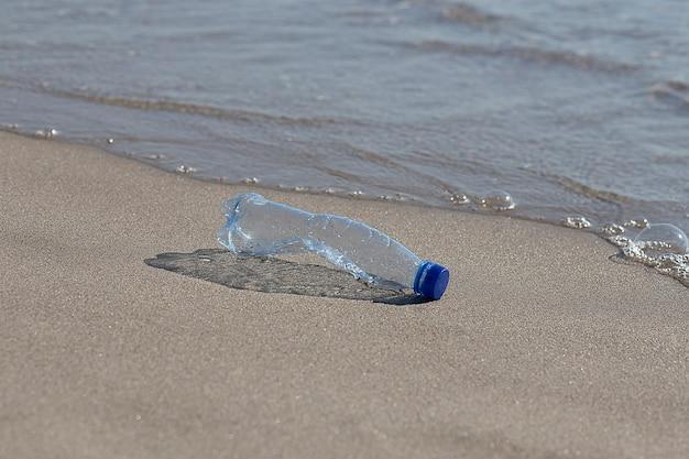 Una bottiglia di plastica giace sulla spiaggia e inquina il mare
