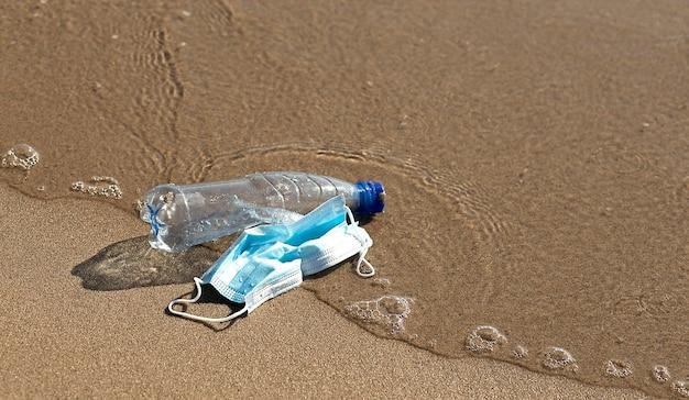 Una bottiglia di plastica giace e una maschera medica sulla spiaggia e inquina il mare