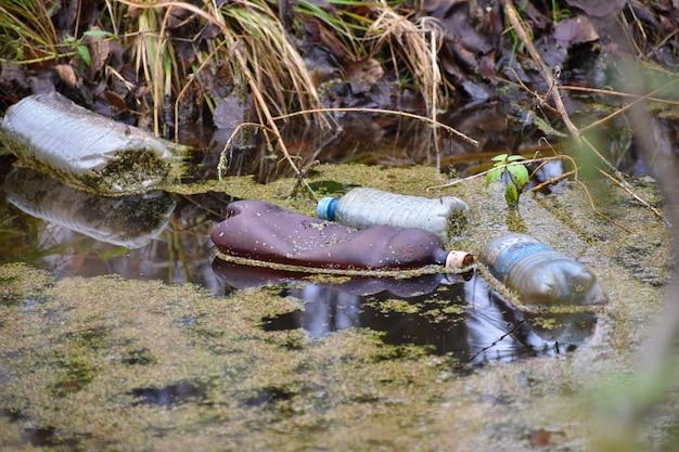 Bottiglia di plastica nel fiume. intasamento ambientale.
