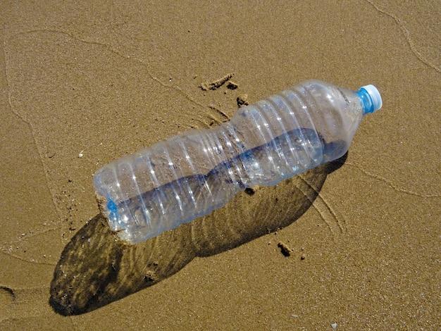 Bottiglia di plastica sulla sabbia in spiaggia, ridurre, riutilizzare e riciclare la plastica