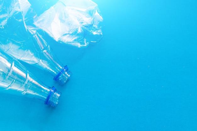 Bottiglia di plastica su uno sfondo blu solido. proteggere l'ambiente. materia prima secondaria. elaborazione dei rifiuti. preservare la natura.