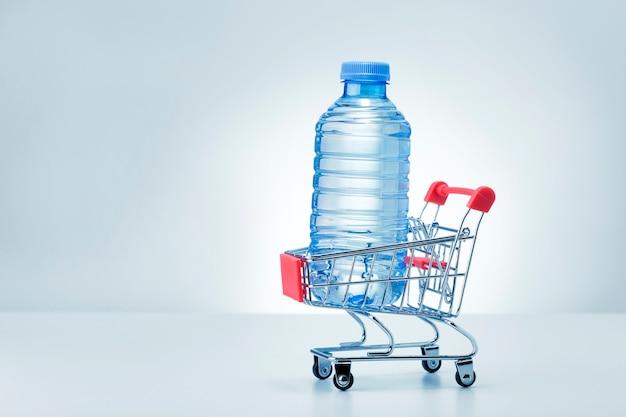 Bottiglia di plastica di acqua nel carrello su sfondo grigio con spazio di copia.