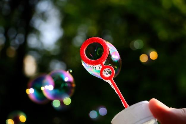 Bottiglia di plastica con bolle di sapone colorate che soffia fotografia ravvicinata con molte bolle