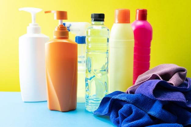 Bottiglie di plastica di prodotti per la pulizia set con pile di vestiti sul fondo della tavola.