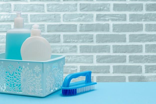 Bottiglie di plastica di detersivo per piatti, detergente per vetri e piastrelle in cestino e un pennello sullo sfondo del muro di mattoni. set di lavaggio e pulizia.