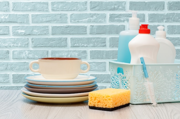 Bottiglie di plastica di detersivo per piatti, detergente per vetri e piastrelle in cestino, piatti puliti e una ciotola sullo sfondo del muro di mattoni. concetto di lavaggio e pulizia.