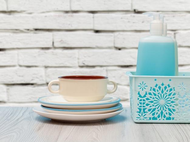 Bottiglie di plastica di detersivo per piatti, detergente per vetri e piastrelle in un cestello, piatti puliti e una ciotola con una parete bianca sullo sfondo. concetto di lavaggio e pulizia.