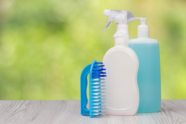 Bottiglie di plastica di detersivo per piatti, detergente per vetri e piastrelle, pennello sullo sfondo naturale sfocato. concetto di lavaggio e pulizia.