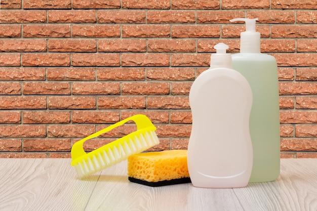 Bottiglie di plastica di detersivo per piatti, detergente per vetri e piastrelle, una spazzola e una spugna con una parete sullo sfondo. concetto di lavaggio e pulizia.