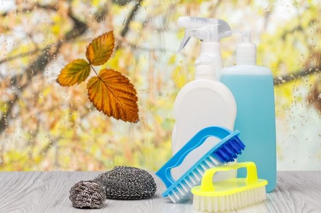 Bottiglie di plastica di detersivo per piatti, detergente per vetri e piastrelle, spazzole e spugne metalliche davanti alla finestra con gocce d'acqua e foglie d'autunno. concetto di lavaggio e pulizia.
