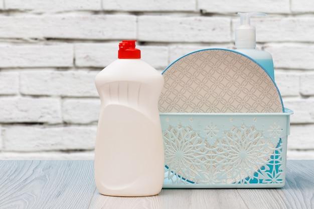 Bottiglie di plastica di detersivo per piatti, detergente per vetri e piastrelle, un piatto pulito in un cesto con una parete bianca sullo sfondo. concetto di lavaggio e pulizia.