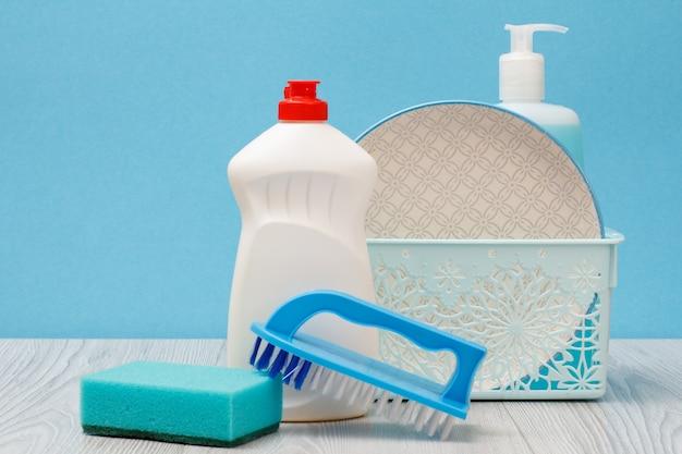 Bottiglie di plastica di detersivo per piatti, detergente per vetri e piastrelle, piatti puliti nel cestello, spazzola e spugna su sfondo blu. concetto di lavaggio e pulizia.