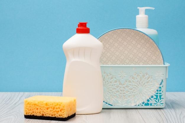 Bottiglie di plastica di detersivo per piatti, detergente per vetri e piastrelle, piatti puliti nel cestello e spugna su sfondo blu. concetto di lavaggio e pulizia.
